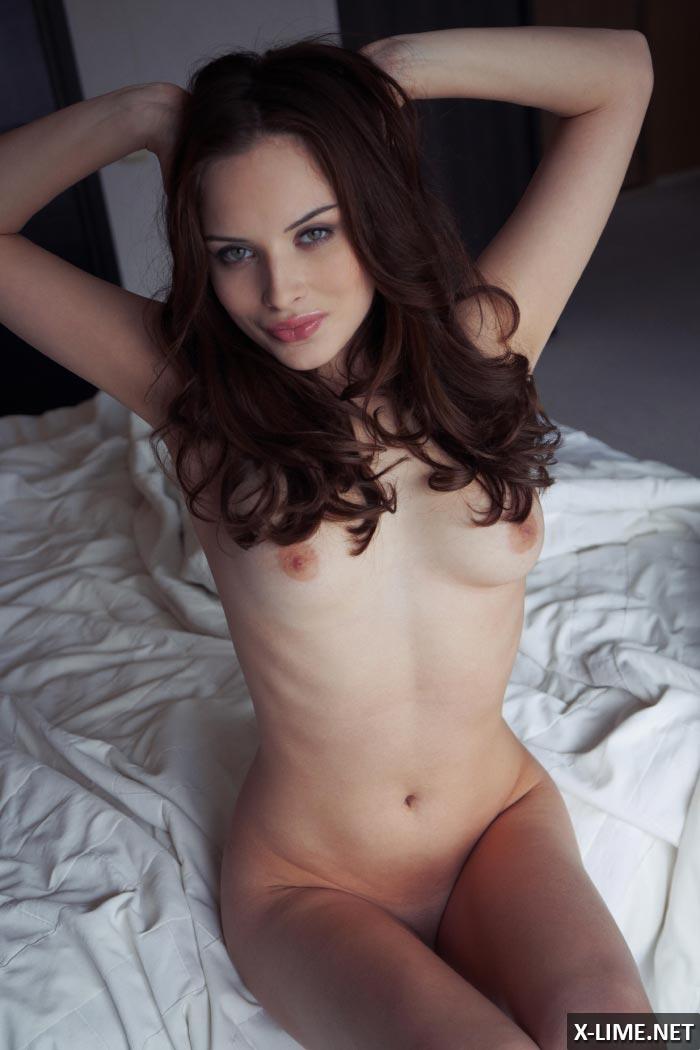 Голая шатенка позирует на кровати, эротическая фотосессия
