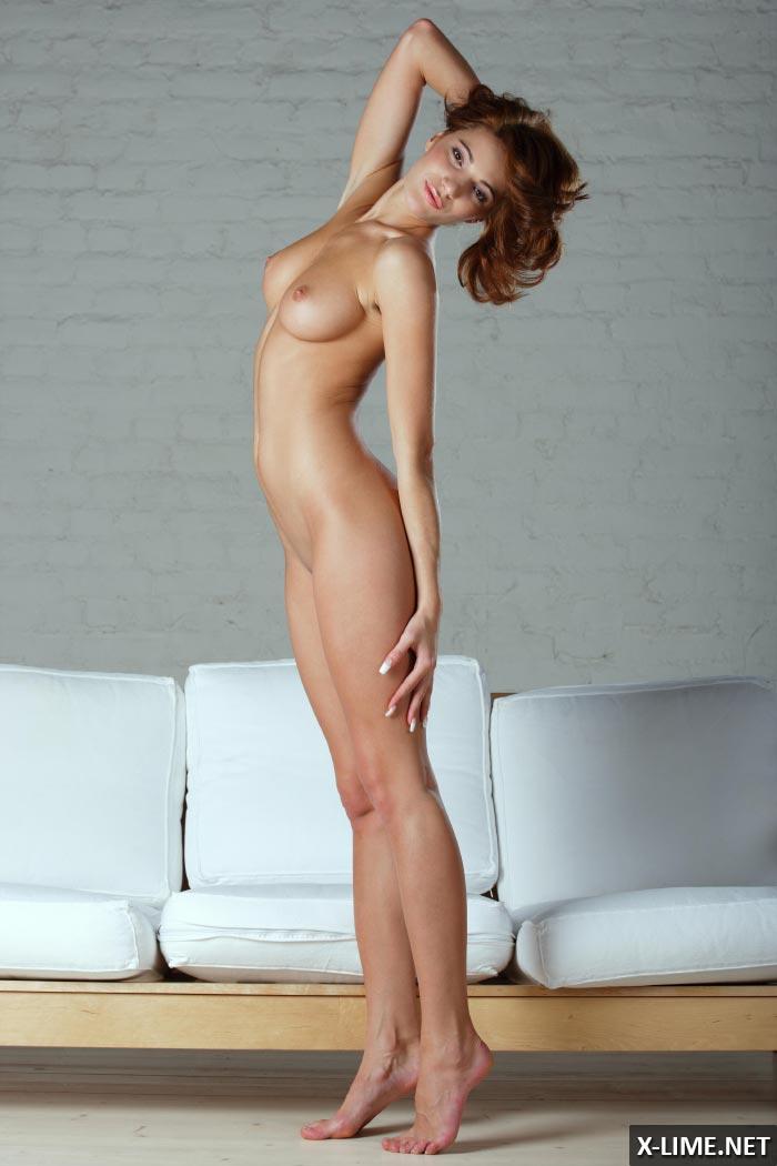 Голая рыжая девушка позирует на диване