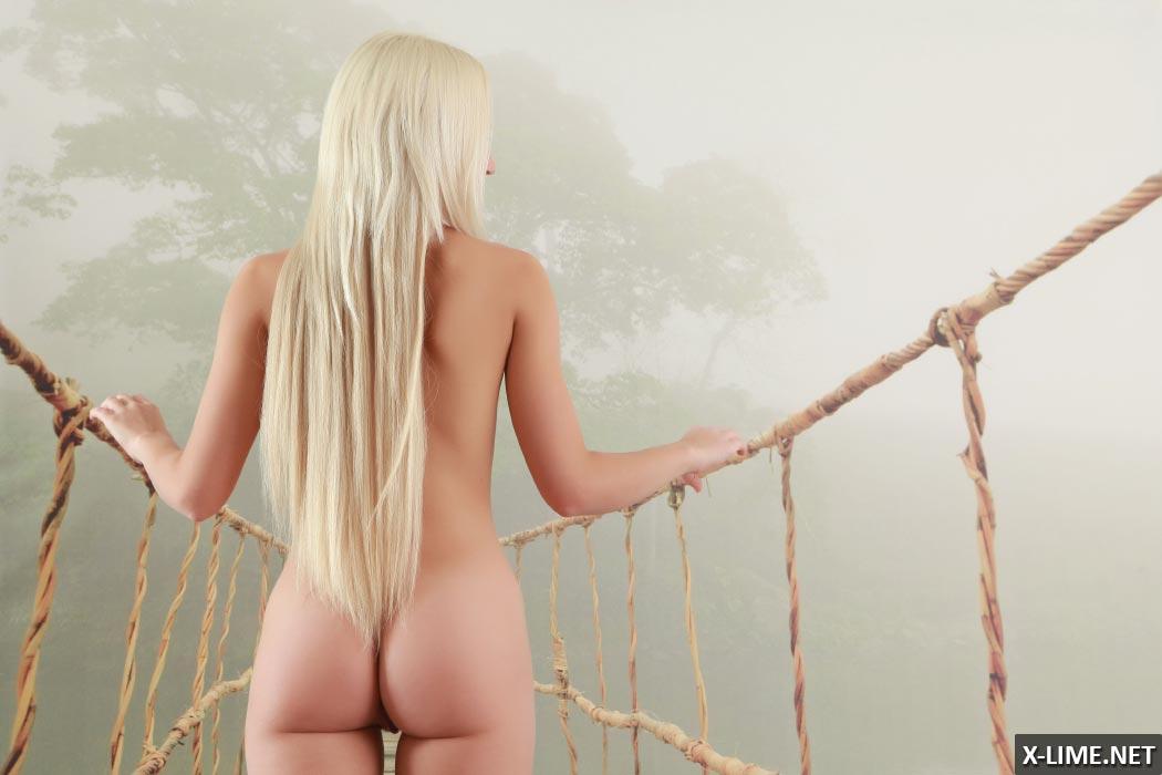 Молодая блондинка с упругой попкой позирует на диване