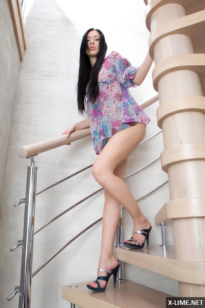 Молодая голая брюнетка на лестнице