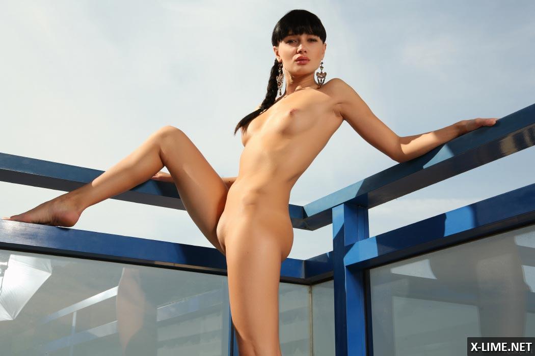 Худенькая голая девушка на балконе