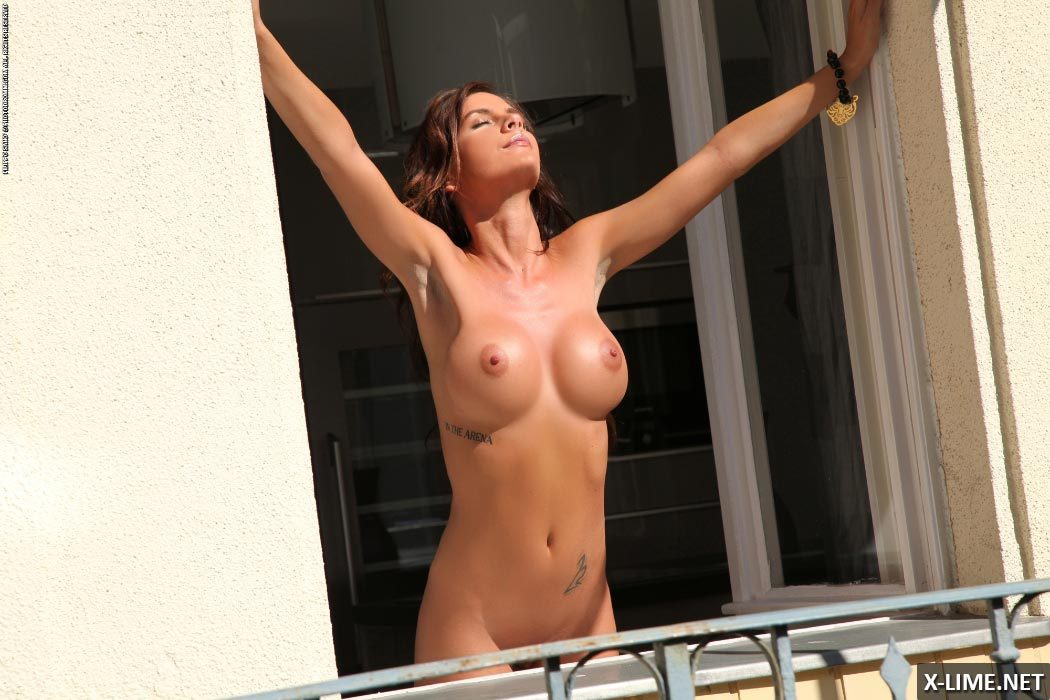 Голая девушка с большими сиськами возле окна